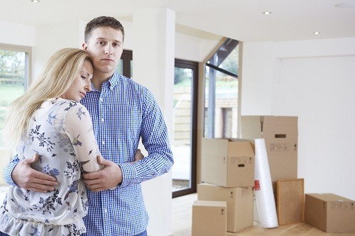 Young Couple With Packed Stuff In House