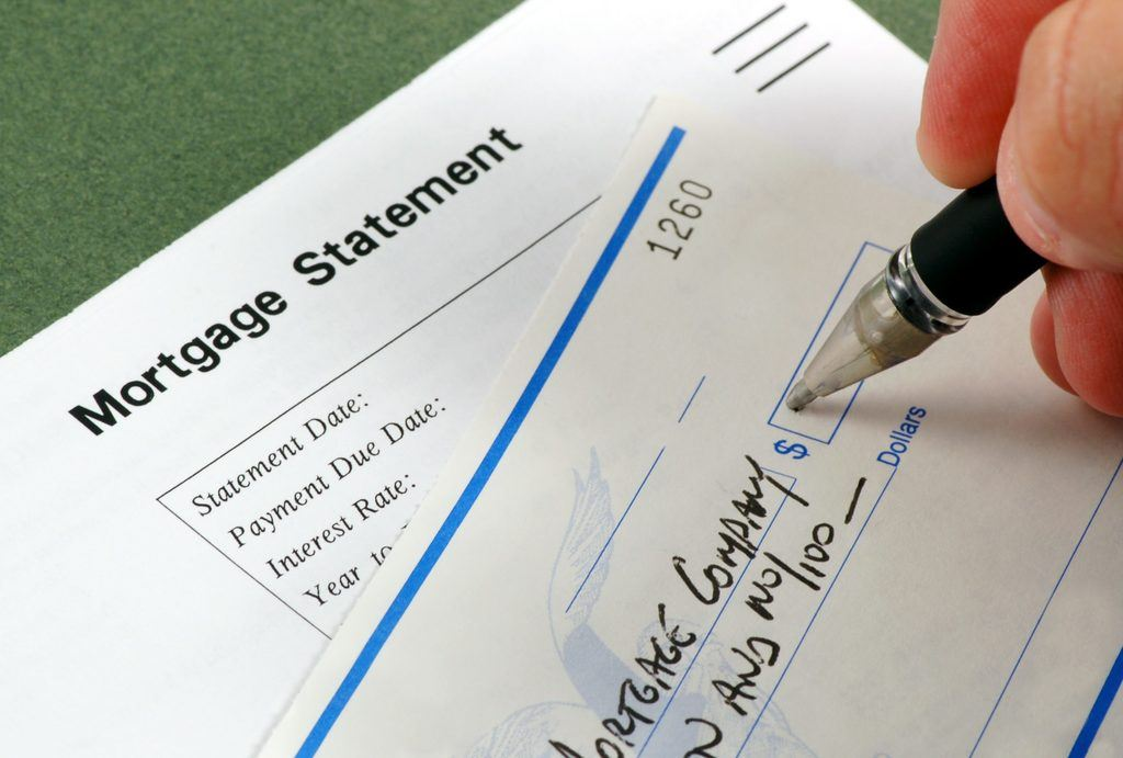 A person filling out a check to a mortgage company