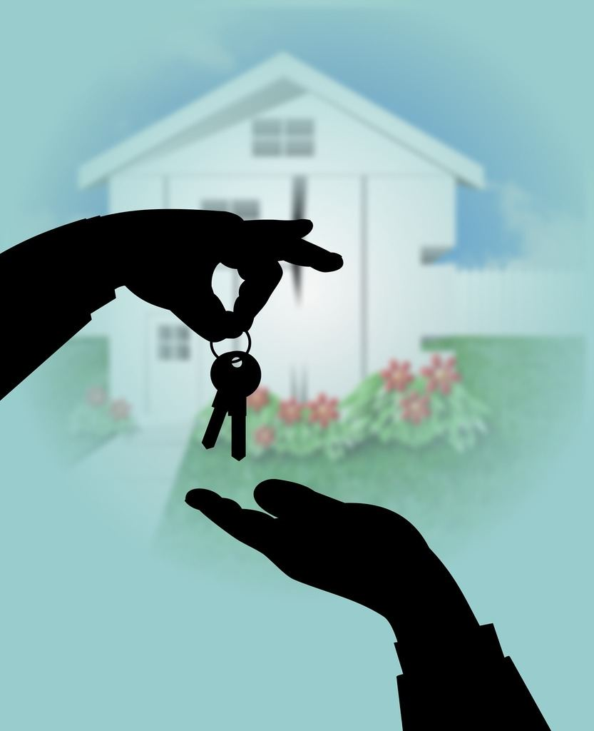 image of a hand giving new home keys to another hand